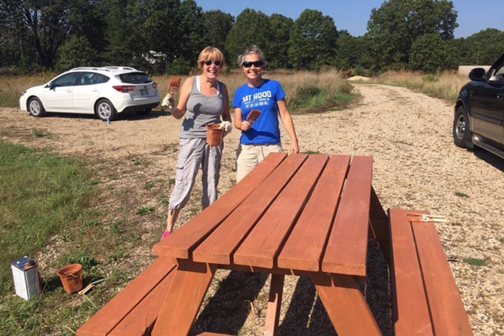 Volunteers staining picnic table